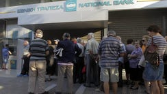 People wait in line outside a National Bank of Greece