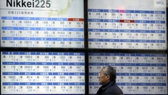 A man looks at an electronic stock board at a securities