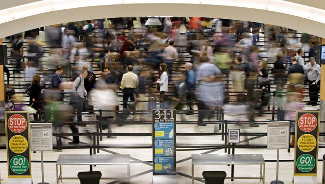 This file photo from Nov. 18, 2010, shows passengers moving through a security line Hartsfield-Jackson Atlanta International Airport.
