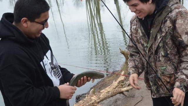 'It's probably the biggest one I've caught at all the lakes,' Omar Cordova, right, of Salem, said about the 12/2-pound trout he caught on Saturday at St. Louis Ponds. His fishing buddy, Eric Lopez, grabbed it for Cordova when he got it up to the bank.