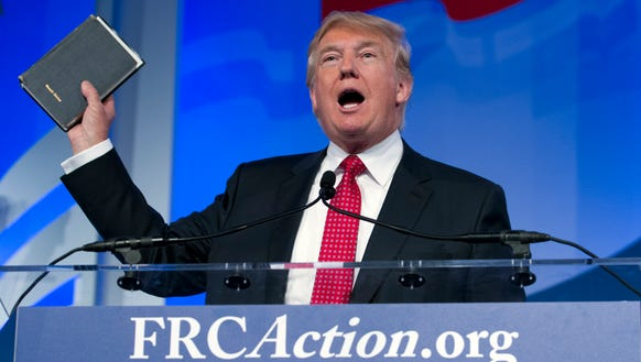 Donald Trump holds up his Bible as he speaks during