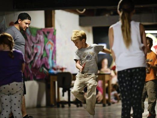 "Joey ""Jolt'n Joey"" Simmons, 9, shows off his breaking moves as Heebz Bruno looks on."