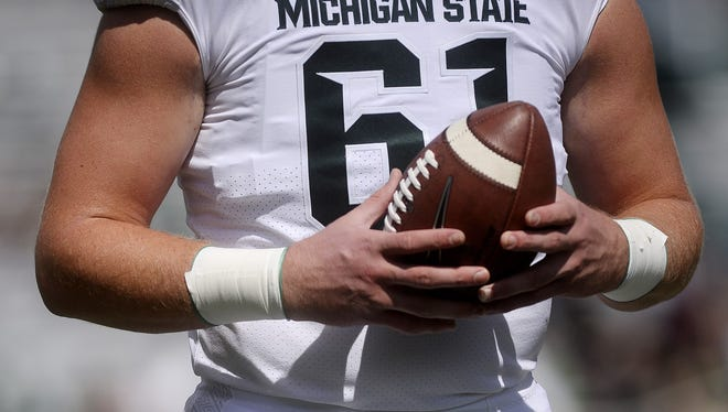Michigan State's Cole Chewins catches a ball during warm-ups before the Spartans' game against Western Michigan on Saturday, Sept. 9, 2017, at Spartan Stadium in East Lansing. The Spartans haven't worn all-white uniforms since 1954.
