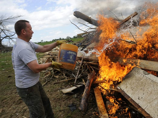 Heath Quick throws diesel fuel on a large debris pile as he helps the Danner's salvage what they can from their destroyed home on Tipton Road Wednesday, April 30, 2014 in Fayetteville, TN.