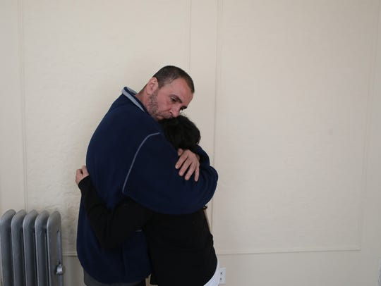 Danny Ramos hugs his partner, Lizette Garcia, after