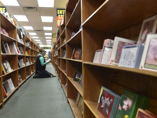 Mariah Sixel of Nasawaupee selects books from Book World, 30 N. Third Ave., Sturgeon Bay. The store plans to close in mid-January.