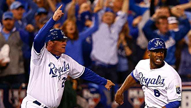 Kansas City Royals third base coach Mike Jirschele waves Lorenzo Cain home with what turned out to be the winning run of the clinching game of the ALCS against the Toronto Blue Jays on Friday, Oct. 23, 2015, in Kansas City.