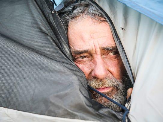 James Royce Jordan looks out his tent under the Houston