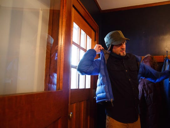 Jeff Wiggins, Des Moines' active transportation planner, puts on his coat Feb. 7 before riding from his home near Drake University to his job in downtown Des Moines.
