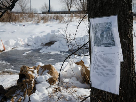 A notice from the city to residents of a homeless encampment hangs in a tree on Friday, Feb. 9, 2018, in Des Moines. It warns residents along the railroad tracks between Mulberry Street and Martin Luther King Parkway that they will be removing belongs in the area on Feb. 26.