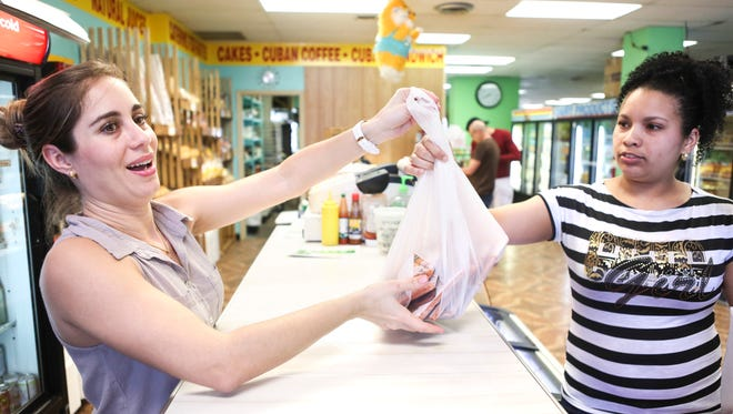 """Yanara Cespedes Popo, left, hands a bag of grocery items to customer Marile Montano inside Bodega Mi Sueno, a Cuban grocery located at 3415 Bardstown Road. Cespedes Popo moved to America from Cuba just five months ago, following her husband, Juan Pablo, that has lived in the U.S. for four years. """"There are more opporunities in this country to study and to work,"""" Cespedes Popo said. """"I like it. I like the people and the city."""" Cespedes Popo believes many more Cubans will migrate to America in the coming years. March 15, 2016"""
