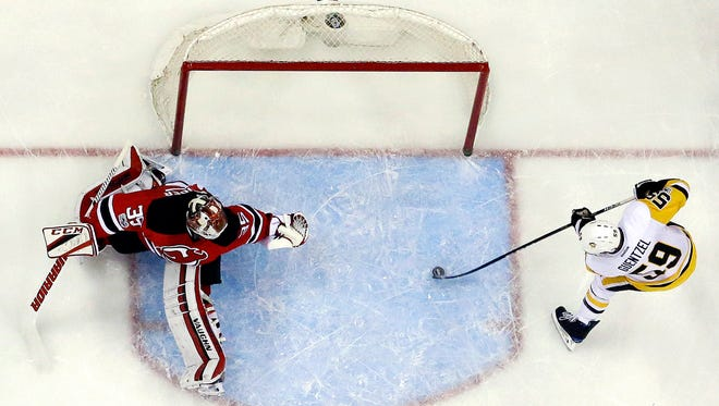 Pittsburgh Penguins center Jake Guentzel, right, prepares to score a goal on New Jersey Devils goalie Cory Schneider, left, as defenseman Michael Kapla tries to help defend during the first period of an NHL hockey game, Thursday, April 6, 2017, in Newark, N.J. The Penguins won 7-4. (AP Photo/Julio Cortez)