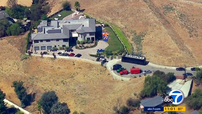This image from aerial video provided by KABC-TV shows the home of entertainer Chris Brown with a police vehicle outside, in the Tarzana area of Los Angeles Tuesday, Aug. 30, 32016. Authorities waited for a search warrant outside Brown's Los Angeles home Tuesday after a getting a woman's call for help, officials said. Inside, the entertainer, who has a history of legal problems, posted videos to social media declaring his innocence.