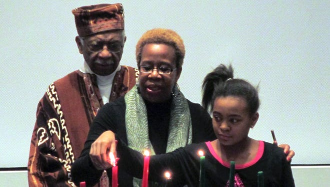 Members of the Rochester Kwanzaa Coalition light a candle on the Kinara during a past Kwanzaa celebration at the Rochester Museum and Science Center. The Kinara holds seven candles, each representing one of the seven principals of Kwanzaa. (Provided)