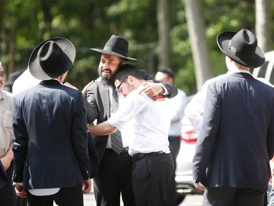 A Rabbi consoles a group of young men after leading