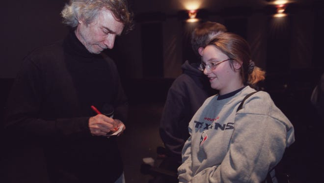 """Director Curtis Hanson signs an autograph for a fan at a premiere for """"8 Mile"""" at the Phoenix Theatre in Detroit in 2003."""
