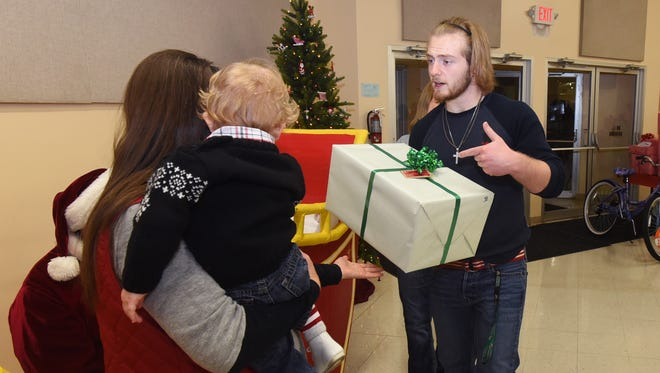 Lucas Johnson helps a family with their presents at the annual Curtain Climber party Wednesday at the Ross County Fairgrounds.