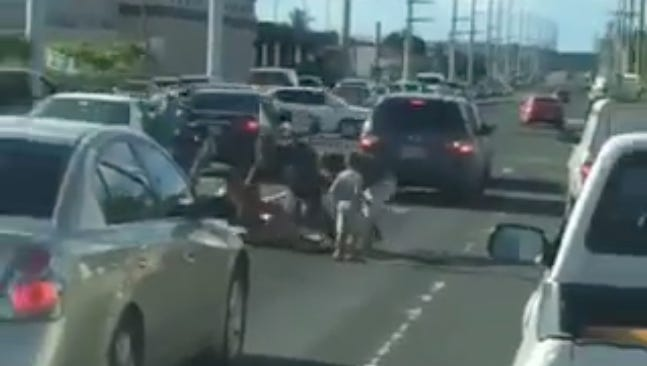 Adults fight while a child looks on in this screen capture from a video released by the Guam Police Department Aug. 31