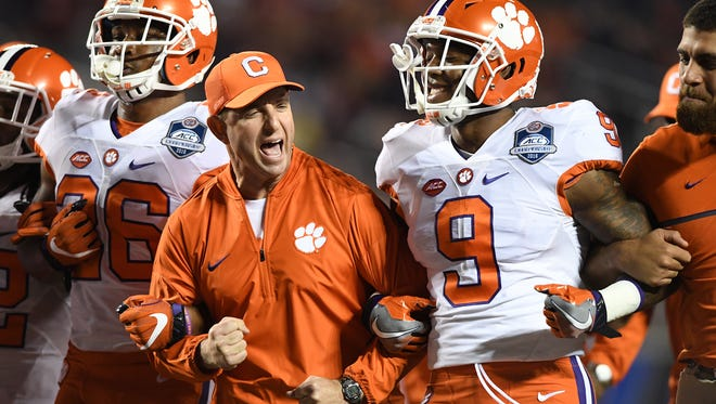 Clemson head coach Dabo Swinney pumps his fist while locking arms with Wayne Gallman (9) and Adam Choice (26) during pregame of the ACC Championship at Camping World Stadium in Orlando on Saturday, December 3, 2016.