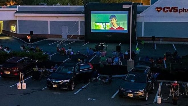 """Cars in the first row enjoy a showing of """"Ferris Bueller's Day Off"""" on Saturday in the parking lot of The Galley Hatch and CVS. It was the third straight Saturday a movie was shown, and Galley Hatch owner John Tinios expects at least four more weeks of movies to come. Tickets for each Saturday showing go on sale the day before at 10 a.m."""