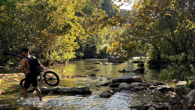 A biker crosses Barton Creek at Lost Creek Park, one of many natural spaces in Central Texas where you can recharge and take a break.