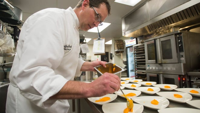Executive chef Jeffrey Blackwell plates dishes during dinner service at Moot House Wednesday, March 9, 2016.