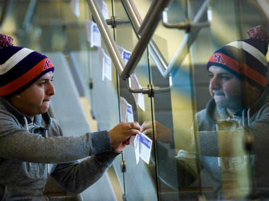 """Felip Cortez, a senior at the University of Evansville, posts some of the """"peace pledges"""" participants in the school's annual Martin Luther King Jr. Day march filled out on the stairwell in the Ridgway University Center during a past year's celebration."""