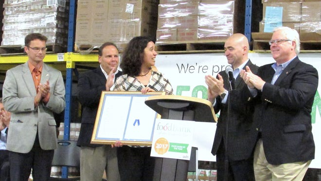 Food Bank of the Southern Tier President Natasha Thompson receives a plaque from several state lawmakers Thursday recognizing the agency's designation as 2017 Food Bank of the Year by Feeding America. From left, state Assemblyman Christopher Friend, Assemblyman Phil Palmesano, Thompson, state Sen. Fred Akshar and Sen. Tom O'Mara.