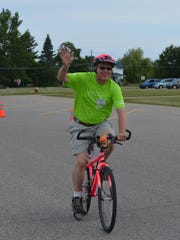 """Michigander Director Barry Culham approaches the 2015 ride's finish line at Cheboygan High School on July 18. He is retiring after serving 18 years as popular bike tour's leader. """"Barry FINALLY crosses the finish line!"""" longtime Michigander volunteer Bob Paull joked."""