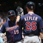 Minnesota Twins' Max Kepler (26) celebrates his grand slam home run as he arrives home with Kennys Vargas against the Texas Rangers during the fifth inning of a baseball game, Sunday, July 10, in Arlington, Texas.
