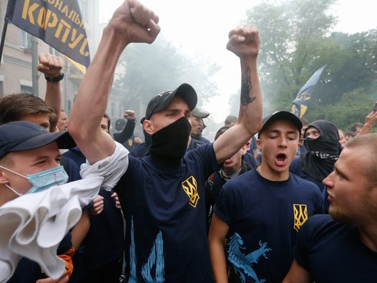 Ukrainian activists react during their rally in front