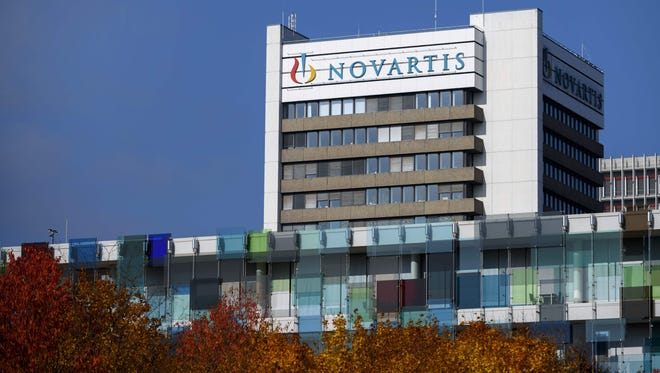 A sign of Swiss pharmaceutical giant Novartis on the top of a building at the company's campus in Basel.