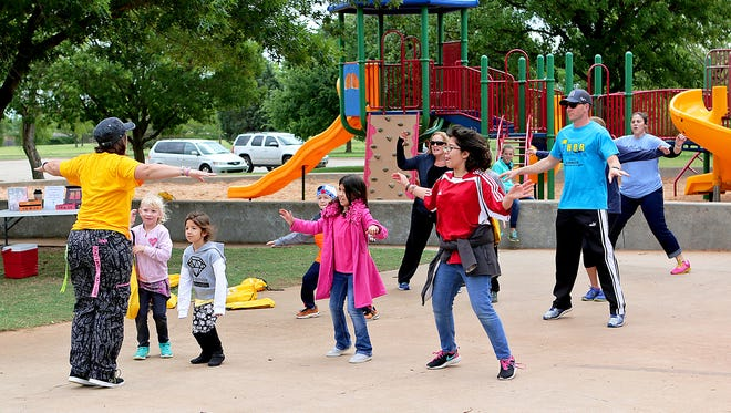 Several children and adults participate in Zumba Saturday morning at the YMCA's Healthy Kids Day in the Kiwanis Park.
