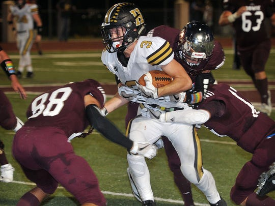 Henrietta Bearcat ball carrier Mason Marchman (3) braces for impact as he is tackled by a host of Bowie Jackrabbits during second quarter action Friday night in Bowie.