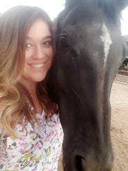Alexandria Claycomb nuzzles her horse, Chilly. Claycomb