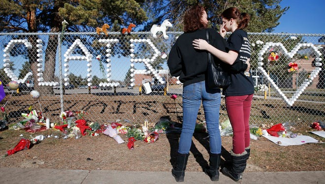 Arapahoe High School junior Emily Evans, right, and her mother Cristina hug while visiting a makeshift memorial bearing the name of wounded student Claire Davis, who was shot by a classmate three days earlier, in front of Arapahoe High School in Centennial, Colo.