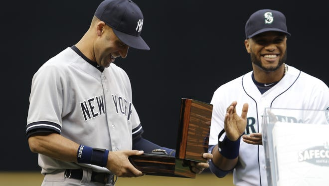 The Yankees' Derek Jeter, left, is given a watch as a gift from former teammate and current Seattle Mariner Robinson Cano, right, during a pregame ceremony honoring Jeter's career on Tuesday night.