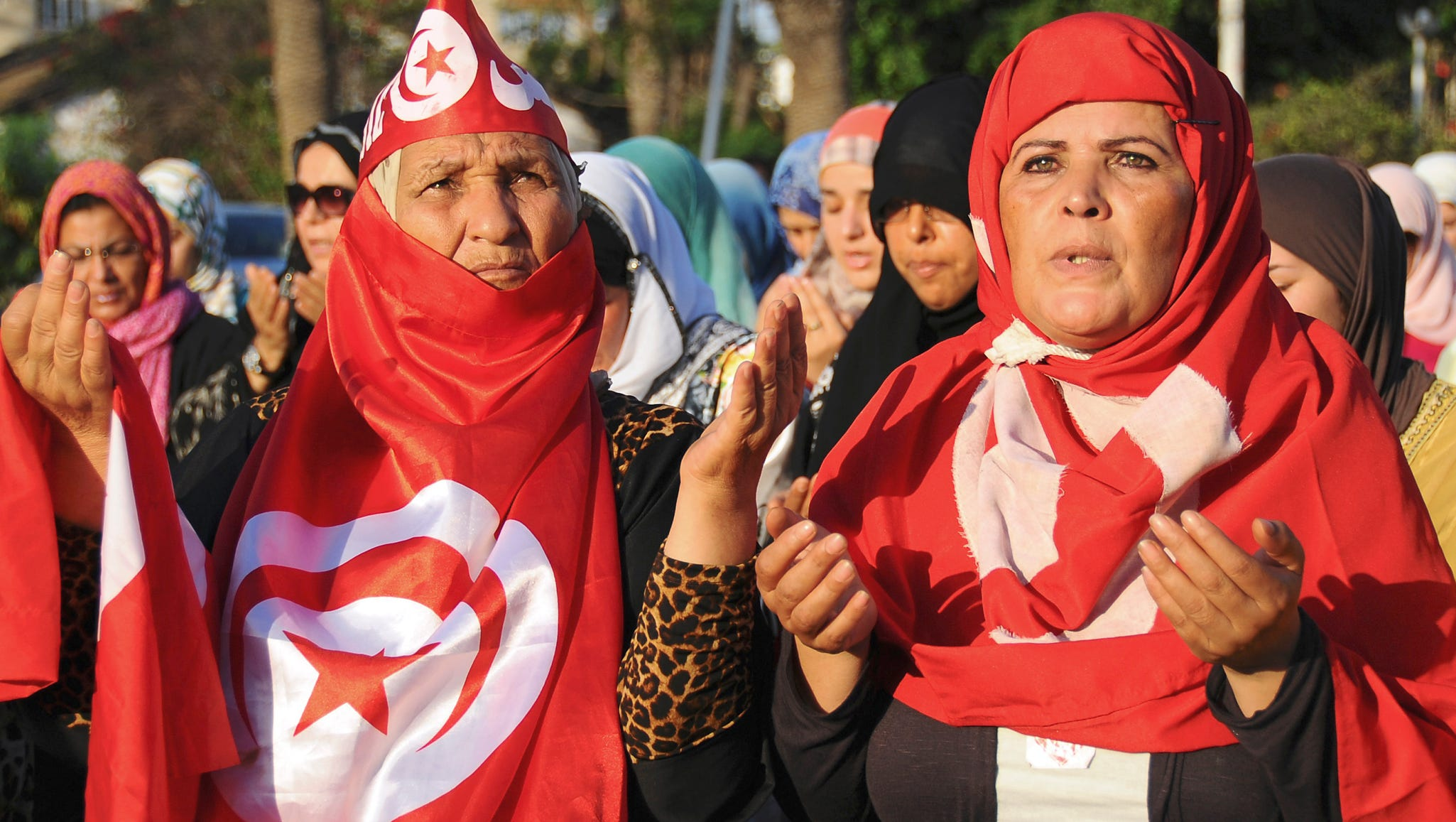 Women wrapped in Tunisian national flags pray near the Zitouna Mosque in Tunis.