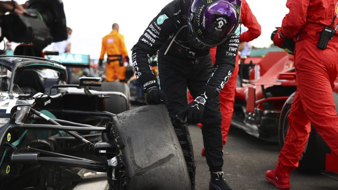 Leiws Hamilton inspects a puncture on his car after winning the British Formula One Grand Prix at the Silverstone racetrack in England on Sunday.