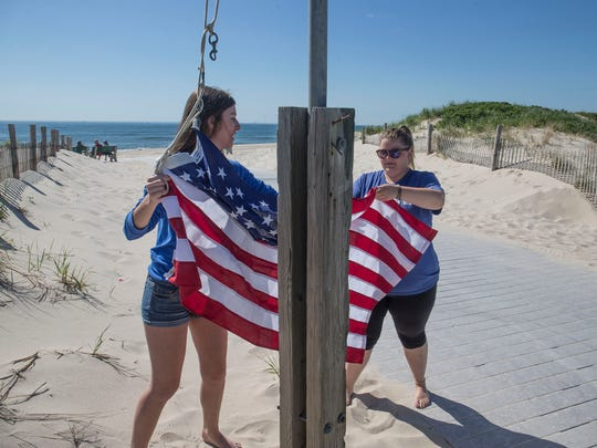 Seaside Park Beach Control employees raise the flag at the 7th Avenue beach entrance earlier this year.