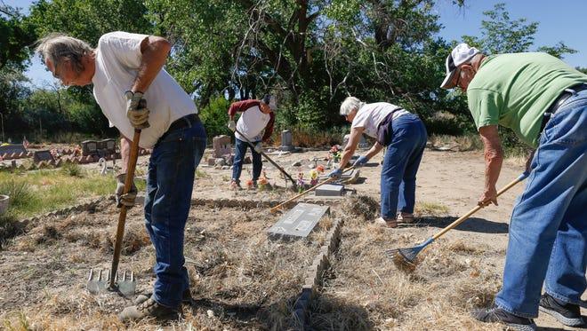 Aztec Senior Center members Paul Priester, left, Felipe Valasquez, June Lange and Don Strode work on a volunteer clean-up project Thursday at the Aztec Cemetery.
