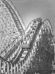 With arms stretched skyward, riders scale one of the peaks of the Rolling Thunder roller coaster at Six Flags Great Adventure.