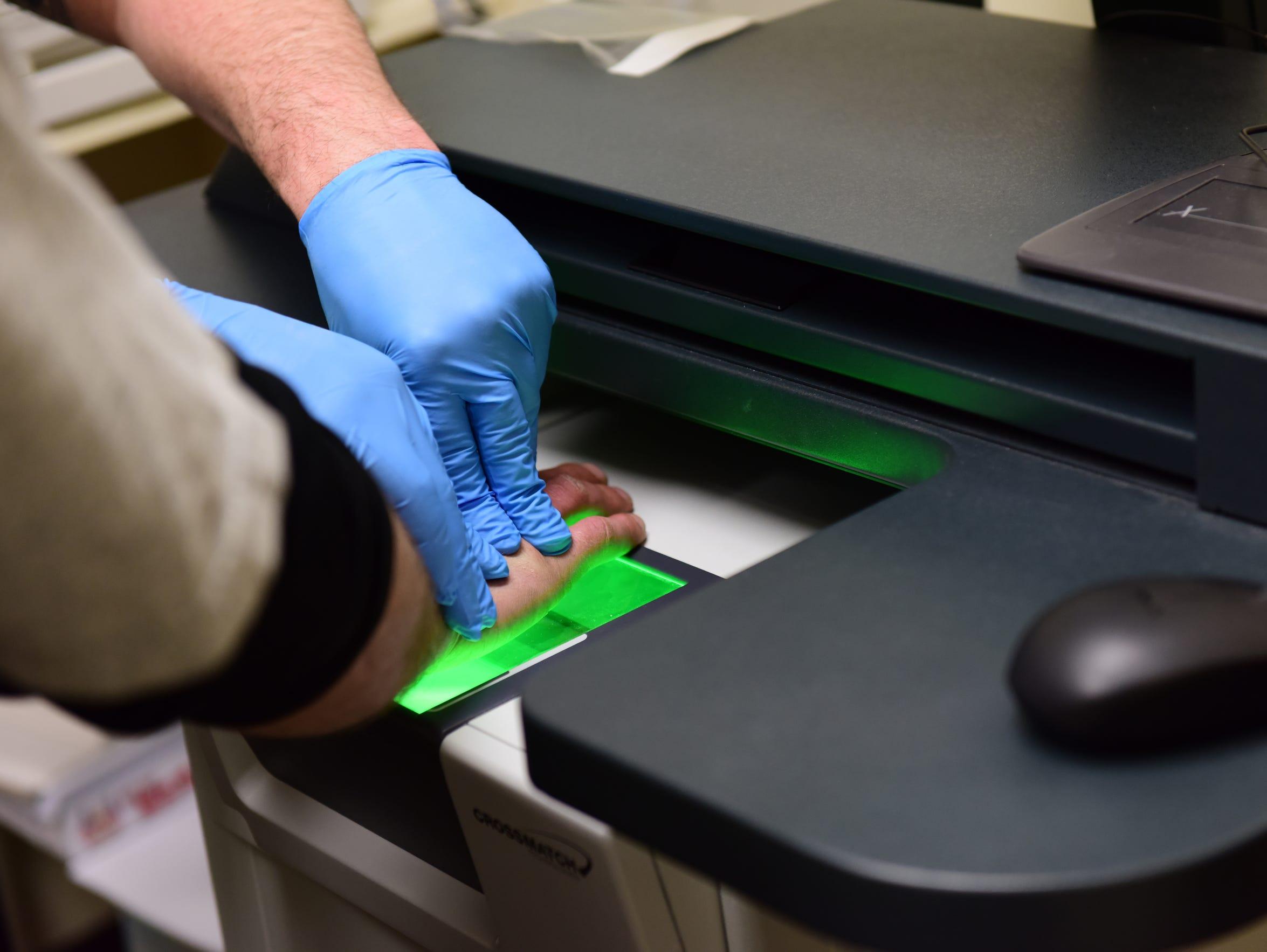 A man is fingerprinted after being arrested for alleged