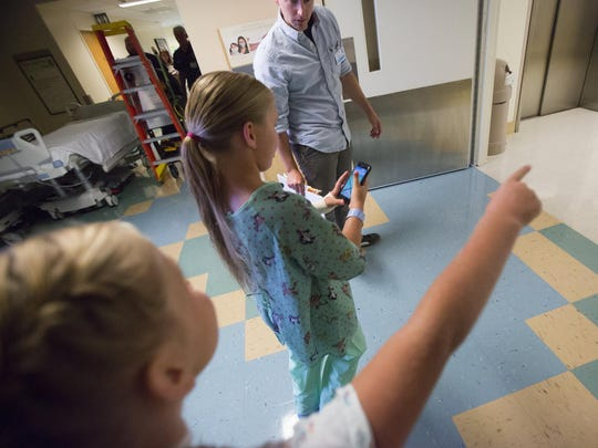 Tyler Medick, Harborview Medical Center research assistant in Rehabilitation Medicine, supervises Priscilla Wagoner, center, and her twin sister Olivia as they hunt for Pokemon.