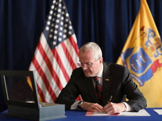 In this photo provided by the New Jersey Office of the Governor, N.J. Gov. Phil Murphy signs the Medical Aid in Dying for the Terminally Ill Act Friday, April 12, 2019 at the New Jersey Statehouse in Trenton, N.J. New Jersey is the seventh state to enact a law permitting terminally ill patients to seek life ending medication.