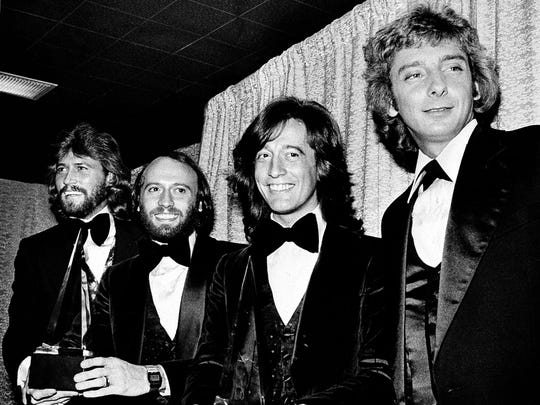 Members of the Bee Gees pose with Barry Manilow, far