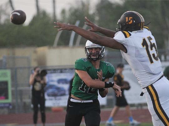 Thousand Oaks High quarterback Hudson Volk throws a pass before Newbury Park's Kyle Stanback can knock it down during Friday night's game.