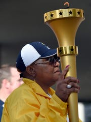 Lu porter holds the torch after walking the last leg of the day for the Indiana Bicentennial Torch Relay that stopped  in downtown Evansville Saturday.  The torch is traveling 3200 miles through each of the 92 counties in Indiana before arriving in Marion County in October.