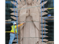 A man works on the 30-foot tall statue of the Virgin