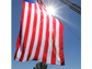 The sun peeks from behind a giant flag at a funeral